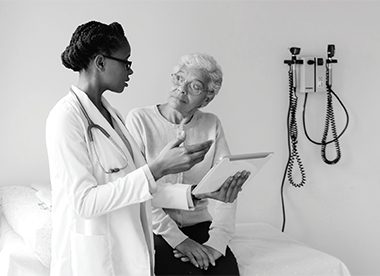 Picture of african female doctor talking with ederly patient